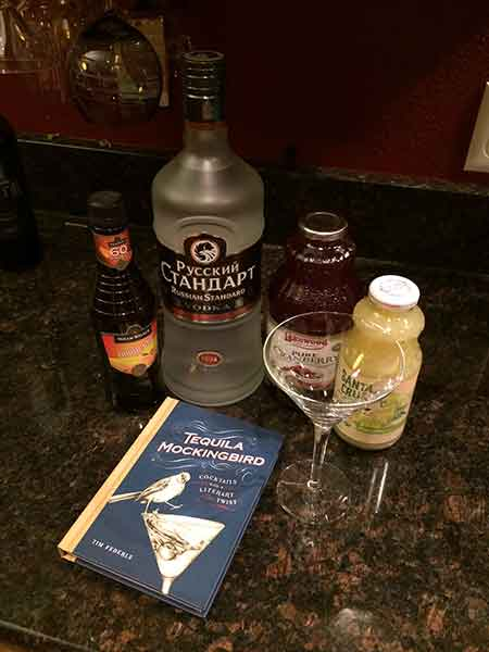 A martini glass next a copy of the book Tequila Mockingbird and bottle of triple sec, vodka, cranberry juice and lime juice.