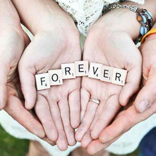 A man's hands cup a woman's hands which cup Scrabble tiles laid out to spell forever.