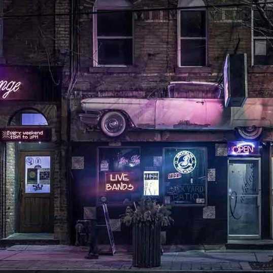 Entrance to a bar with neon signs in the windows and above the doors. The profile of a Cadillac hangs above the door and next to a sign that says Cadillac Lounge.