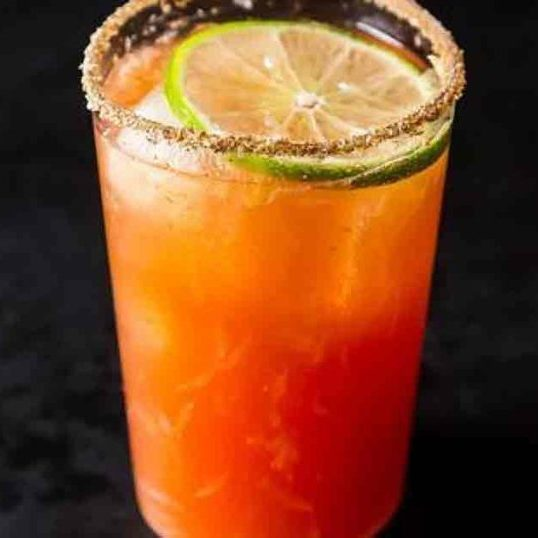 A tall glass of cerveza preparada with chili salt around the rim and a lime in the beer and hout sauce mix.