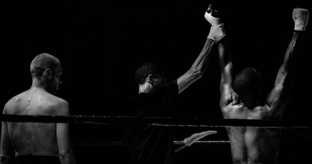 Two boxers, backs to the camera, stand in a ring. The referee lifts one boxer's hands into the air, in victory.