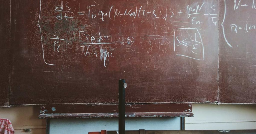 A red chalkboard with advanced math written on it.